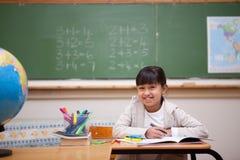 Lächelnde Schulmädchenzeichnung auf einem Malbuch Lizenzfreie Stockbilder