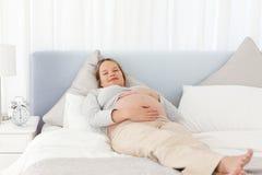 Lächelnde schwangere Frau, die auf einem Bett sich entspannt Lizenzfreies Stockbild