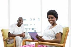 Lächelnde schwangere Frau, die digitale Tablette und den Mann sitzt auf Stuhl verwendet Lizenzfreie Stockfotografie