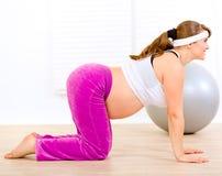 Lächelnde schwangere Frau, die Eignungübungen tut Stockbild
