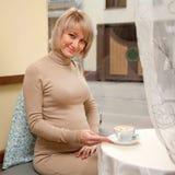 Lächelnde schwangere Frau, die frühstückt Lizenzfreies Stockbild