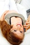 Lächelnde schwangere Frau, die sich zu Hause auf Couch entspannt Lizenzfreies Stockfoto