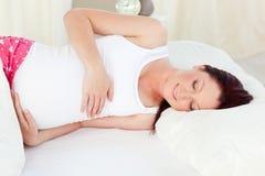 Lächelnde schwangere Frau, die zu Hause in ihrem Bett stillsteht Lizenzfreie Stockfotografie