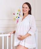 Lächelnde schwangere Frau im Kindertagesstättenraum Stockfotos