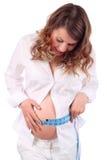 Lächelnde schwangere Frau misst Bauch durch Zentimeterband Stockfotos