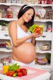 Lächelnde schwangere Frau mit einer Platte des Frischgemüsesalats Lizenzfreie Stockfotografie