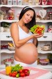 Lächelnde schwangere Frau mit einer Platte des Frischgemüsesalats Stockbilder