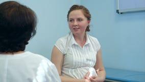 Lächelnde schwangere Frau mit ihrem Doktor im Krankenhauszimmer Stockfoto