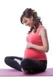 Lächelnde schwangere Frau umfasst Bauch während des Yoga Lizenzfreie Stockfotos