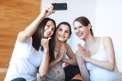 Lächelnde schwangere Frauen machen Fotos von selbst auf einem Smartphone in der Turnhalle nach einem Training stockbild