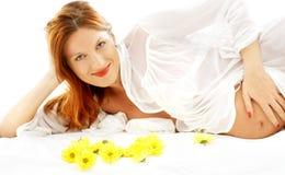 Lächelnde schwangere Schönheit mit Blumen Lizenzfreie Stockfotos