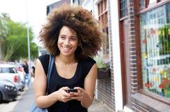 Lächelnde schwarze Frau, die auf Bürgersteig mit Handy geht Lizenzfreies Stockfoto