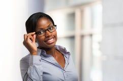 Lächelnde schwarze Frau, die ihre Brillen hält stockfoto