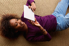 Lächelnde schwarze Frau, die sich mit digitaler Tablette hinlegt Lizenzfreie Stockfotos