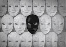 Lächelnde schwarze Maske unter weißen Masken, heuchlerisch Konzept Stockfoto