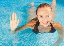 Lächelnde Schwimmen des jungen Mädchens des Bonbons im Pool Stockbild