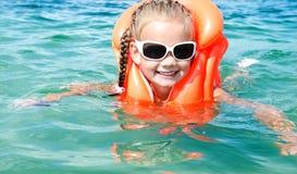 Lächelnde Schwimmen des kleinen Mädchens mit Schwimmweste Stockfotos
