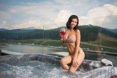 Lächelnde sexy Frau mit perfektem Körper im Bikini, der am Jacuzzi mit Cocktail sitzt und zur Kamera schaut Lizenzfreie Stockbilder