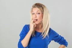 Lächelnde sexy junge Frau, die, ihren Finger für Zweifel beißend zögert Lizenzfreies Stockfoto