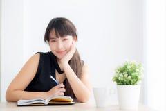 Lächelnde sitzende Studie der schönen jungen asiatischen Frau und Lernen, Notizbuch und Tagebuch in das Wohnzimmer zu Hause schre lizenzfreie stockfotos