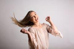 Lächelnde sorglose natürliche temperamentvolle Frau, die langes Haar schlägt lizenzfreies stockfoto