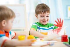 Lächelnde spielende Kinder und Malen Stockbilder