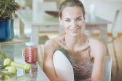 Lächelnde Sportlerin, die gesundes Cocktail trinkt stockfoto