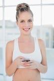Lächelnde sportliche blonde Versenden von SMS-Nachrichten Stockfotos
