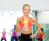 Lächelnde sportliche Frau mit Proteindrinkflasche lizenzfreies stockbild