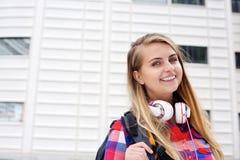 Lächelnde stehende Außenseite des Studenten mit Tasche und Kopfhörern Lizenzfreie Stockfotos