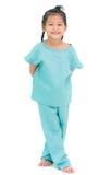 Lächelnde Stellung des asiatischen Mädchens im Krankenhauskleid, lokalisiert auf Weiß lizenzfreie stockfotografie
