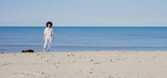 Lächelnde Stellung des kühlen Mannes auf Sand vor dem breiten Schuss des Ozeans stockfotos