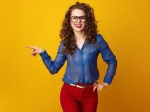 Lächelnde stilvolle Frau in den Gläsern zeigend auf etwas Stockfotografie