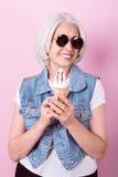 Lächelnde stilvolle Frau, die eine Eiscreme hält Stockfoto