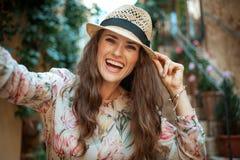 Lächelnde stilvolle touristische Frau in alter Europa-Stadt, die selfie nimmt stockbild