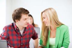 Lächelnde Studenten, die in der Schule einander betrachten Lizenzfreie Stockbilder