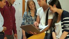 Lächelnde Studenten, die Laptop im Umkleideraum verwenden stock video