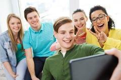 Lächelnde Studenten, die selfie mit Tabletten-PC machen Lizenzfreies Stockfoto