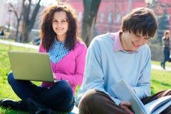 Lächelnde Studenten draußen Stockbilder