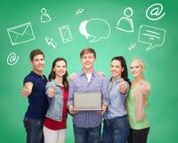 Lächelnde Studenten mit dem Laptop, der sich Daumen zeigt Stockbilder