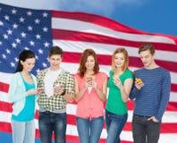 Lächelnde Studenten mit Smartphones Lizenzfreie Stockfotos