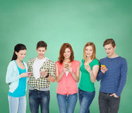 Lächelnde Studenten mit Smartphones Stockfotografie