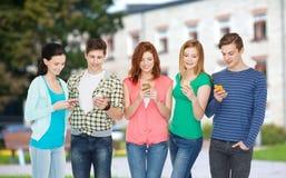 Lächelnde Studenten mit Smartphones Stockfoto