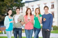Lächelnde Studenten mit Smartphones Stockbilder
