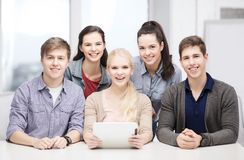 Lächelnde Studenten mit Tabletten-PC in der Schule Lizenzfreies Stockbild