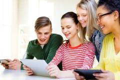 Lächelnde Studenten mit Tabletten-PC in der Schule Stockbild