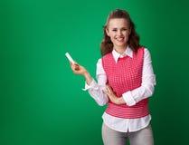 Lächelnde Studentenfrau mit Stück Kreide auf grünem Hintergrund Stockfotos
