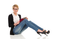 Lächelnde Studentin, die auf dem Boden mit Ringmappe sitzt. Lizenzfreie Stockbilder
