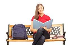Lächelnde Studentin, die auf einer Bank und dem Halten eines Buches sitzt Lizenzfreies Stockbild