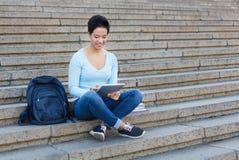 Lächelnde Studentin, die draußen mit Tablette arbeitet stockbild